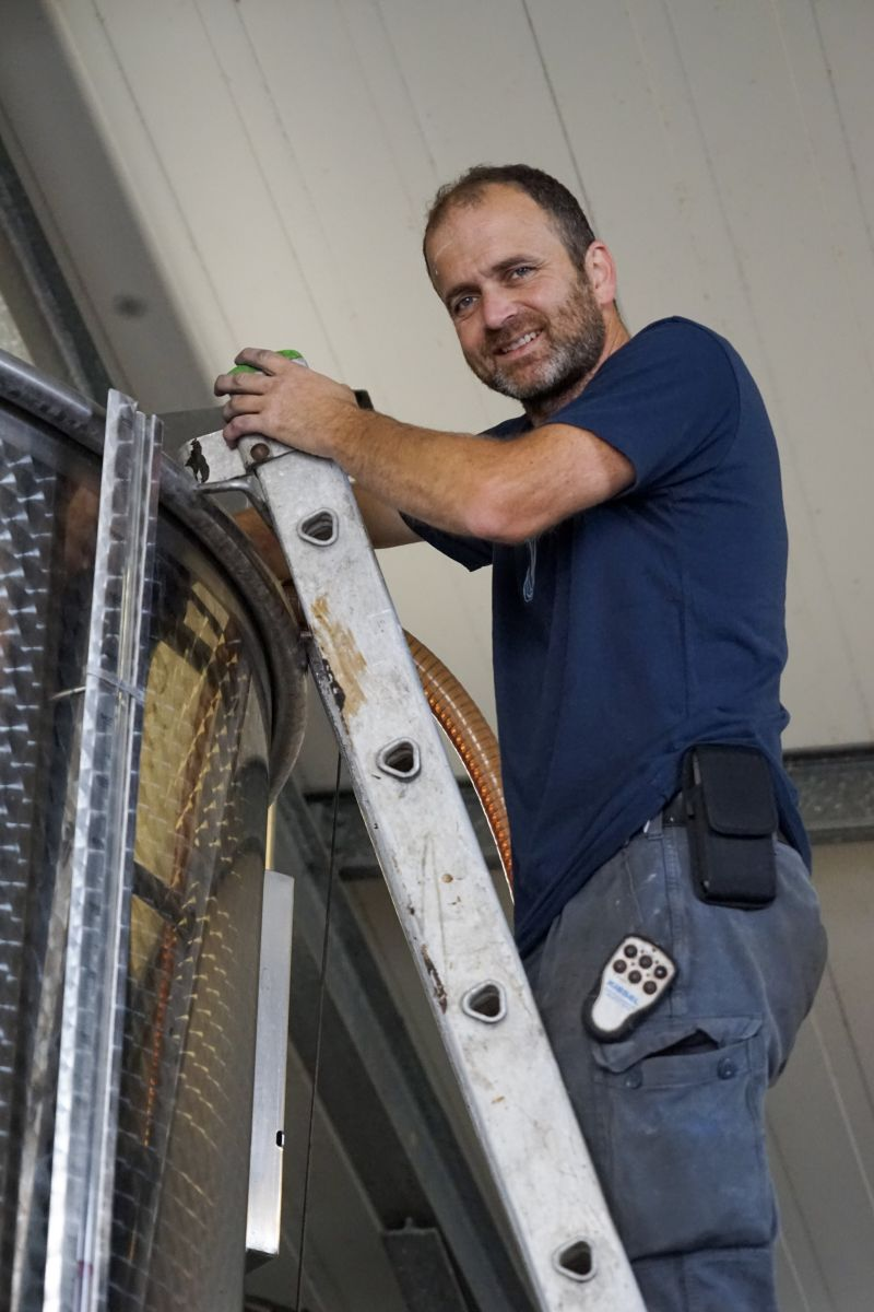 Andreas Roll auf der Leiter am Weintank