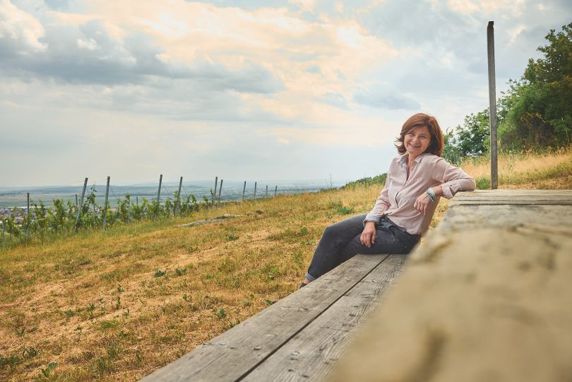 Birgit Braunstein auf einer Bank in Ihrem Weinberg im Burgenland